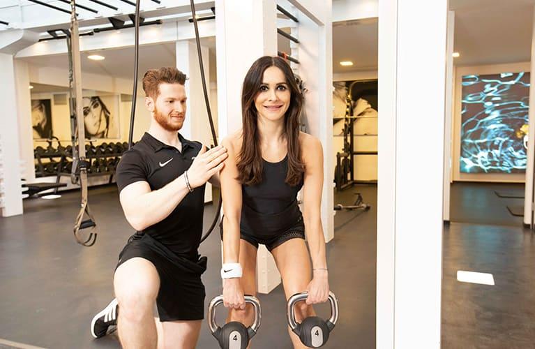 personal trainer bei jonensports beim training mit laechelnder kundin mobil