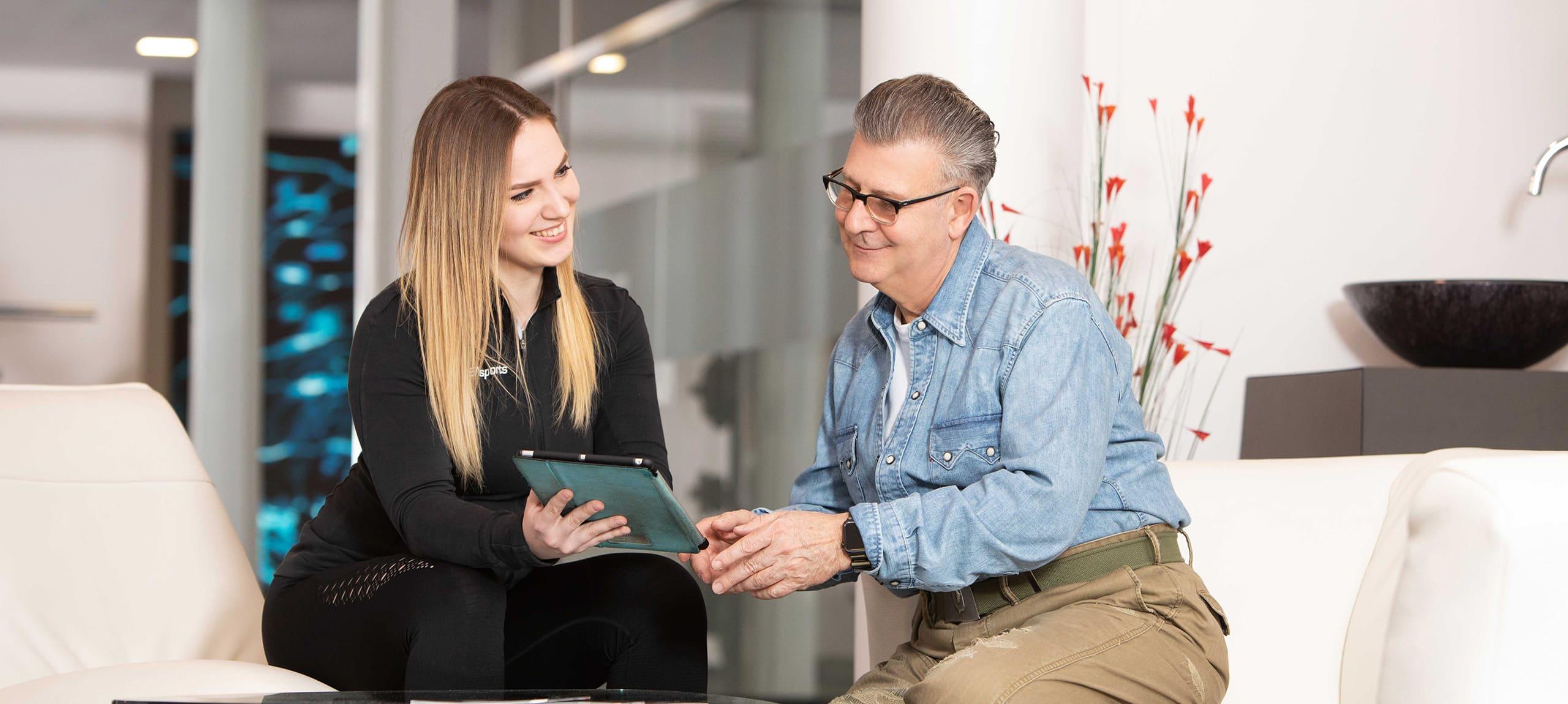 personal trainer zeigt einem kunden seinen fortschritt auf einem tablet