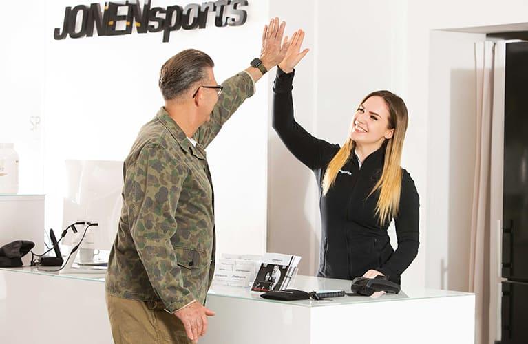 personal trainerin und kunde geben sich high five mobil