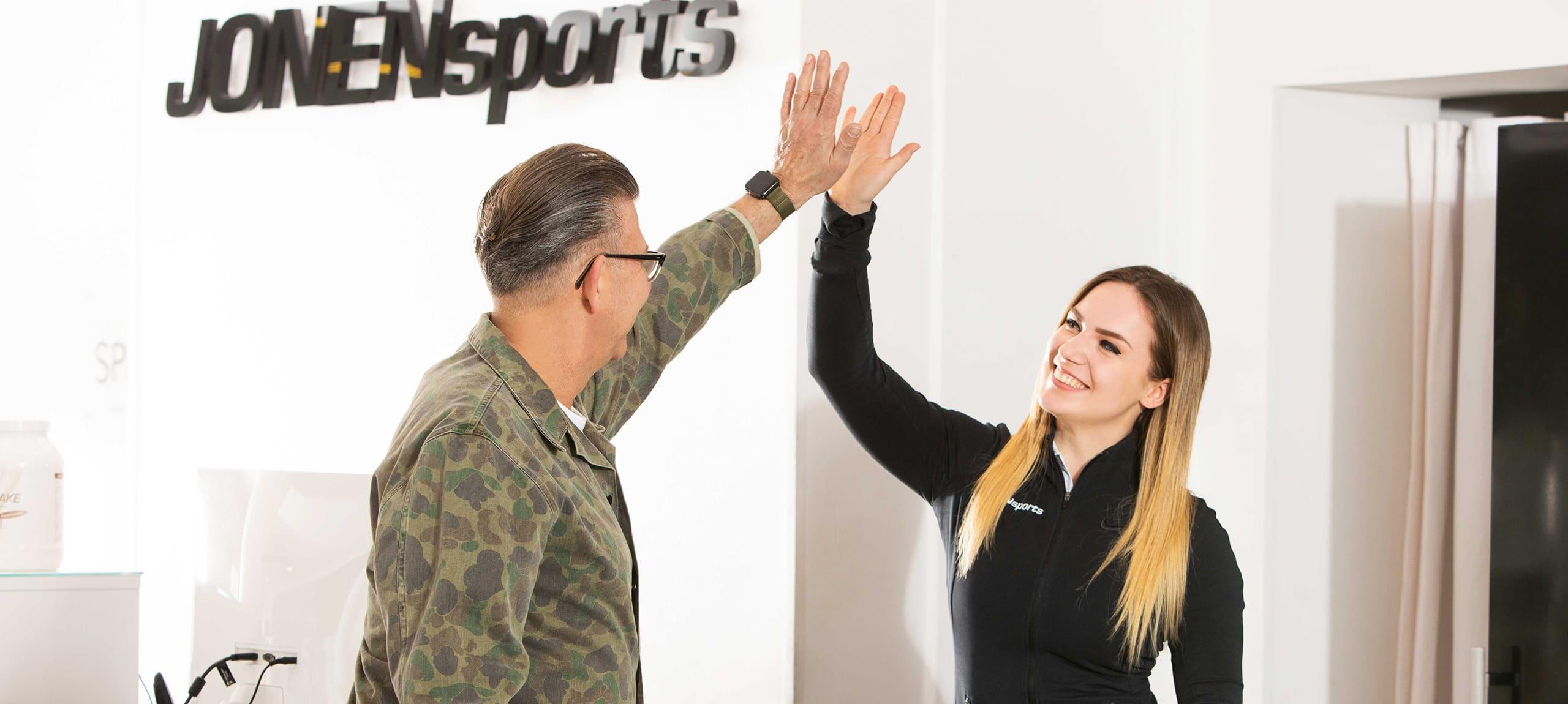 personal trainerin und kunde geben sich high five