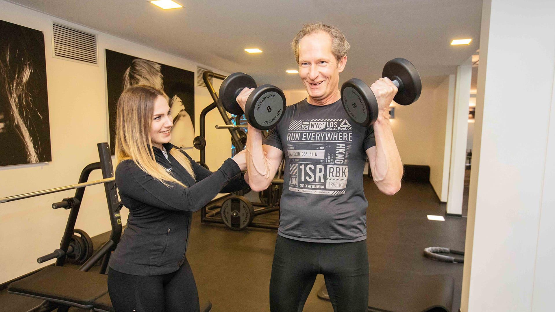 trainerin von jonen sports hilft einem kunden beim freihante training