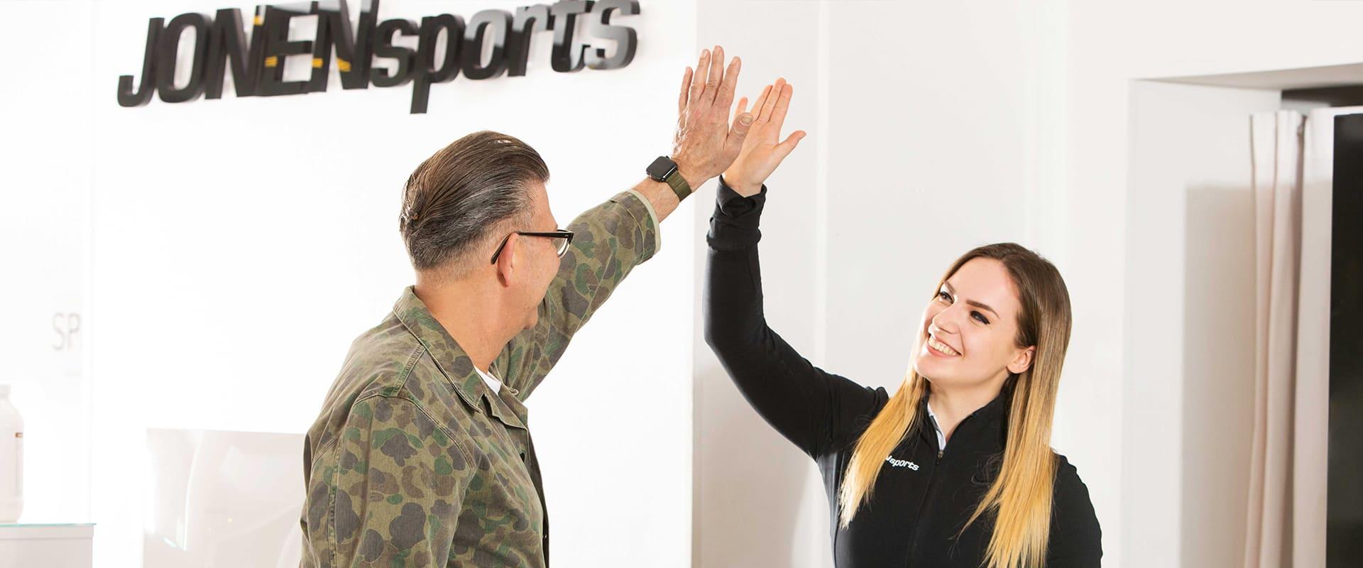 trainerin von jonensports gibt einem kunden high five