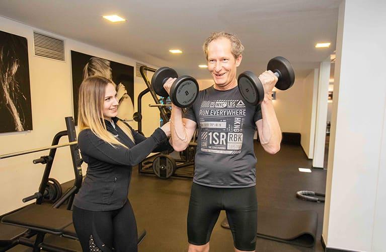 trainerin von jonensports hilft beim freihantel training mobil